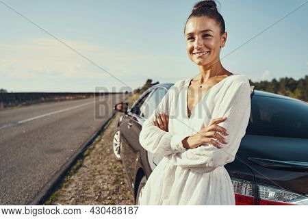 Female Waiting Beside Her Car With Optimistic Smile