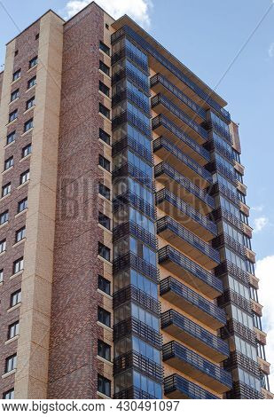 Multistorey Residential Building Made Of Variegated Multicolored Bricks With Glazed Balconies.  High