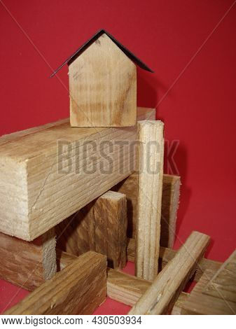 Architectural Composition Of The Modules Of The House Surrounded By Wooden Figures On A Red Backgrou