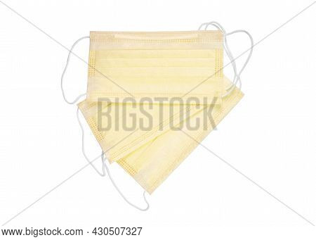 Yellow Protective Face Mask. Disposable Medical Face Mask Isolated On White Background Closeup. Covi