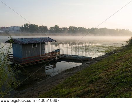Landscape With Sava River And Fishing Hut And Moored Boats During Beautiful Foggy Autumn Morning