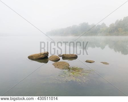 Serene Landscape On River Sava With Rocks And Algae In Water During Beautiful Misty Autumn Morning