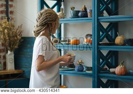 Hostess Of The Ceramic Workshop Lays Out Her Ceramic Dishes On The Shelves. Feng Shui Concept. Small