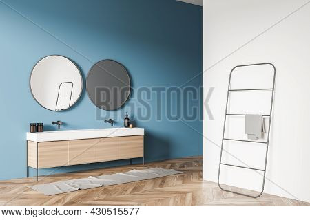 Minimalist Bathroom Interior With Vanity, Two On Trend Round Mirrors On Blue Wall And Towel Rack Nea