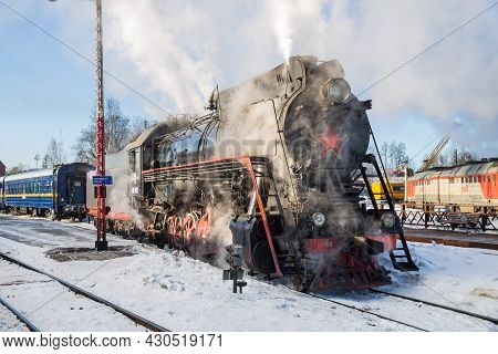 Sortavala, Russia - March 10, 2021: An Old Soviet Steam Locomotive Clings To A Passenger Train At Th