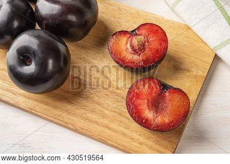 Black Plums Cut In Half And Whole On A Wooden Cutting Board Over White Wooden Table. Large Fresh Plu