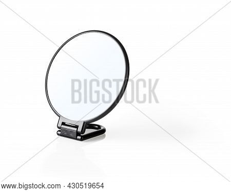 Round Cosmetic Mirror In A Black Plastic Frame Isolated On A White Background. Desktop Makeup Mirror
