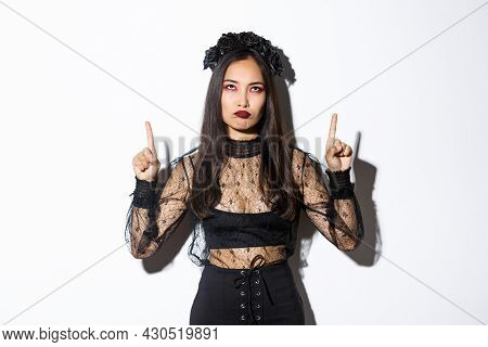 Grumpy Asian Female In Witch Costume Looking Disappointed And Upset, Pointing Fingers Up And Sulking