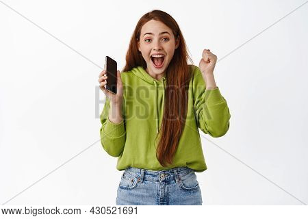 Excited Winning Ginger Girl Celebrating, Winning Money On Mobile Phone, Holding Smartphone And Trium