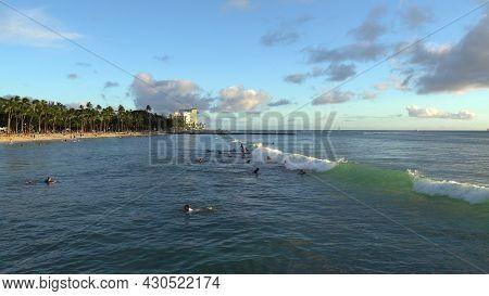 Honolulu, Hawaii - March 15 2021: Gorgeous Sunset On Honolulus Waikiki Beach. Surfers Ride The Waves