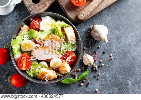 Caesar Salad With Smoked Chicken And Parmesan On A Plate On Dark Background. Top View, Copy Space.