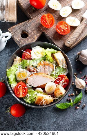 Caesar Salad With Smoked Chicken And Parmesan On A Plate On Dark Background. Top View