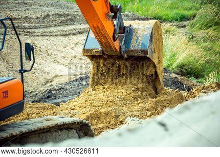 Closeup Bucket Of Backhoe Digging The Soil At Construction Site. Crawler Excavator Digging On Demoli