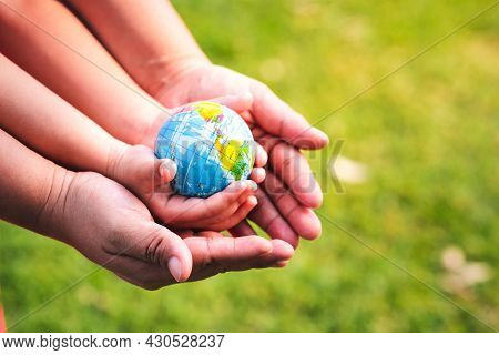 Eco Friendly Concept. The Hands Of Children And Adults Are Holding The World Safe From Global Warmin