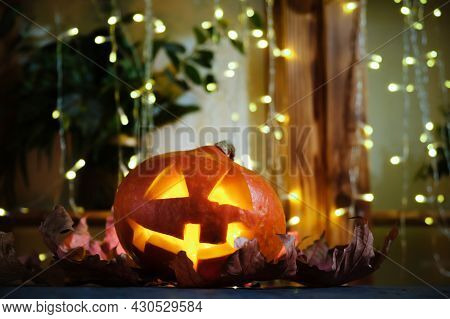 Halloween Party, Holiday Home Decor Concept. Pumpkin Head Illuminated From Inside. Halloween Carved