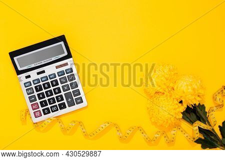 Big Silver Calculator And Flower Bouquet On A Yellow Background With Copy Space. Concept Of Sewing B