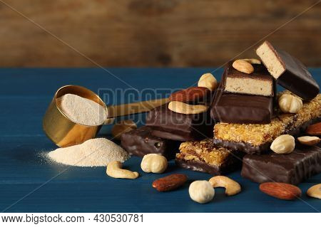 Different Tasty Bars, Nuts And Scoop Of Protein Powder On Blue Wooden Table