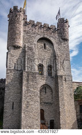 Gent, Flanders, Belgium - July 30, 2021: Frontal View On Gray Stone Main Tower With Flags On Top Of