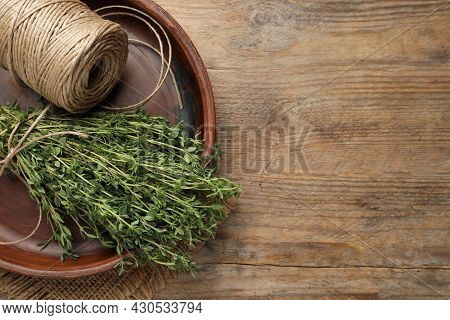 Bunch Of Aromatic Thyme And Twine In Bowl On Wooden Table, Top View. Space For Text