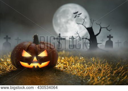 Spooky Halloween Pumpkin In Graveyard At Moonlight With Dead Tree And Bats. Halloween Party And Cele