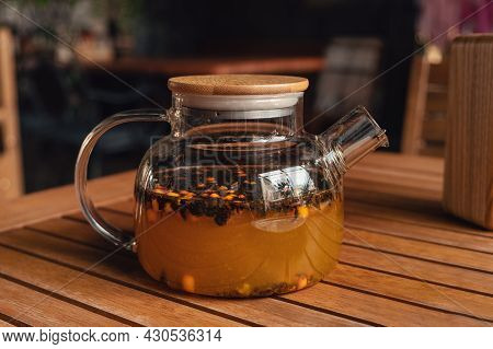 Warming Tea With Sea Buckthorn In Glass Teapot In Cafe. Warm Tea In Cold Autumn Or Winter Weather -