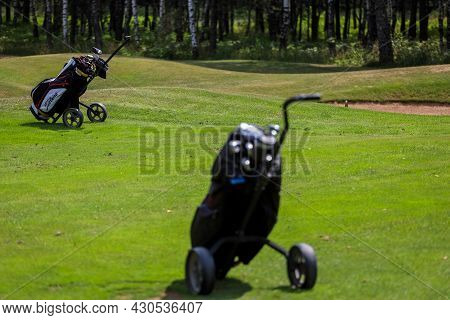 Minsk. Belarus - 24.07.2021 - Push-pull Golf Carts On The Field. Green Grass, Trees. High Quality Ph