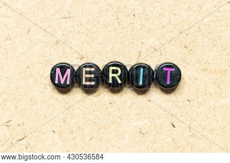 Black Color Round Bead In Word Merit On Wood Background