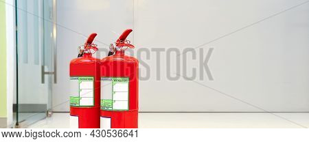 Fire Extinguisher, Close-up Red Fire Extinguishers Tank With Fire Escape Doorway Or Door Exit In The