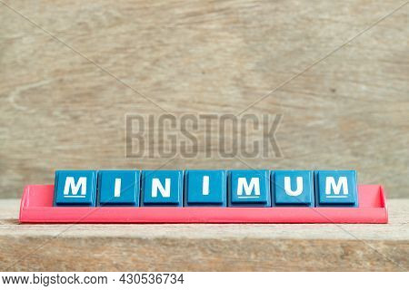 Tile Alphabet Letter With Word Minimum In Red Color Rack On Wood Background