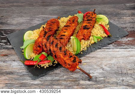 Barbecued Chilli Chicken Meat Kebabs On Wooden Skewers With Rice Meal