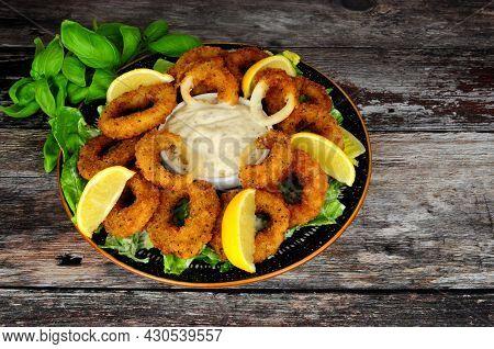 Breadcrumb Covered Salt And Pepper Calamari Squid Rings With Tartar Dipping Sauce And Fresh Lemons
