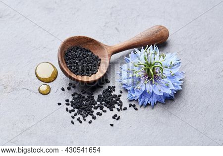 Black cumin seeds with nigella sativa flower on gray stone background