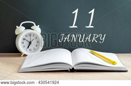 January 11. 11-th Day Of The Month, Calendar Date.a White Alarm Clock, An Open Notebook With Blank P