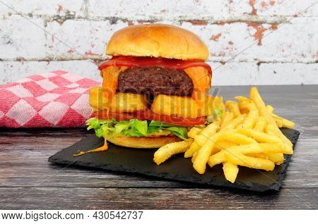 Cheeseburger With Hash Browns And French Fries On A Slate Serving Board