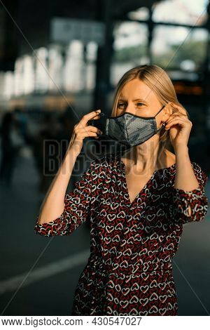 A woman puts an antiviral mask on her face at the train station.