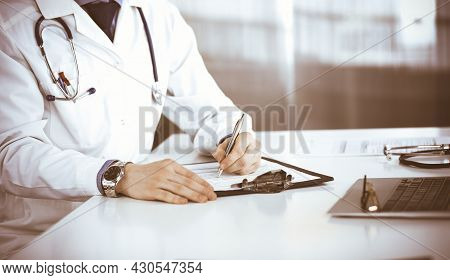 Unknown Male Doctor Sitting And Working With Clipboard Of Medication History Record In Clinic At His