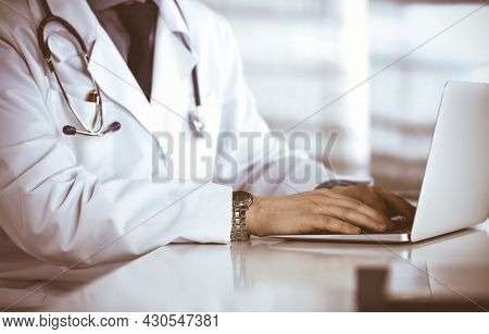 Unknown Male Doctor Sitting And Working With Laptop In Clinic At His Working Place, Close-up. Young