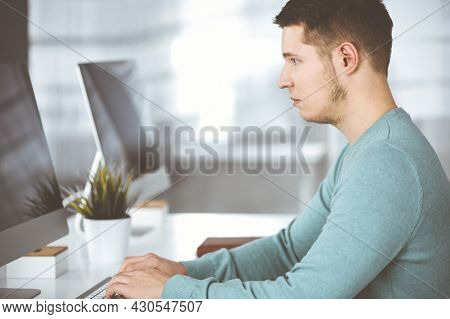 Young Confident Businessman, Wearing A Green Pullover, Is Sitting At The Desk In A Modern Office, Wh