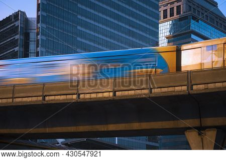 Motion Blur Of Sky Train Moving On Elevated Railway With Glass Business Buildings In Downtown At Ban