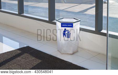 White Hexagon Trash Bin With Black Rubber Doormat On White Tile Floor In Entrance Way Area Of Shoppi