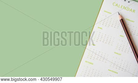 Pencil On White Calendar And Green Background, Top View, For Planning Work ,monthly Or Yearly Schedu