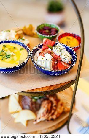 Selection of traditional greek meze: fava, greek salad, stuffed grape leaves and olives