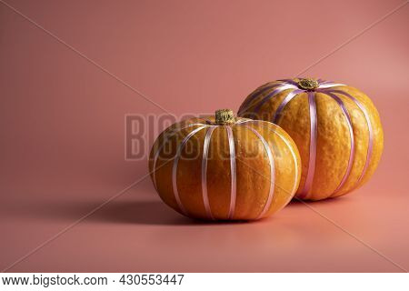 Pumpkins On Pastel Pink Background With Pastel Ribbon. Autumn, Fall, Halloween