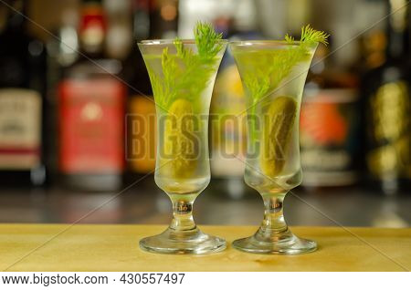 Shaken Vodka And Pickle Juice With Ice In Shot Glass And Garnishing With Small Pickled Cucumber And