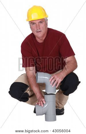 plumber fixing a plastic pipe