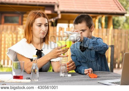 Mom And Son Are Conducting Chemical Experiments At Home. An Experience With A Child About Creating A