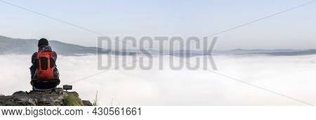 A Female Traveler In The Mountains Sits On The Edge Of A Cliff And Admires A Foggy Morning In The Mo
