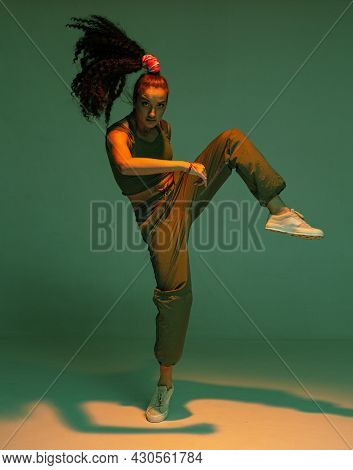 Dancing Mixed Race Girl In Colourful Studio Light. Female Dancer Performing Expressive Hip Hop Dance