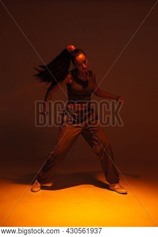 Dancing Athletic Mixed Race Girl Performing Expressive Fiery Hip Hop Or Ethnic Afro Dance In Warm St