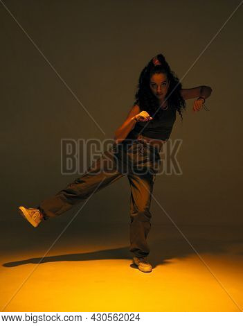 Dancing Mixed Race Girl In Studio Spotlight. Female Dancer Performer Show Expressive Hip Hop Dance